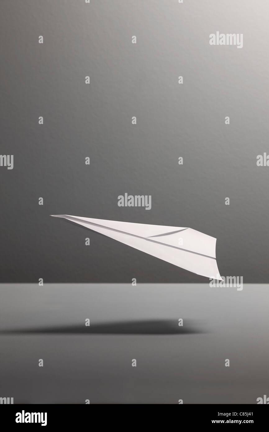 Aeroplano di carta contro uno sfondo grigio Immagini Stock