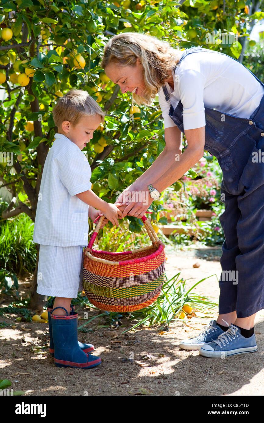 Little Boy aiutare la sua mamma portano cesto di verdure Immagini Stock