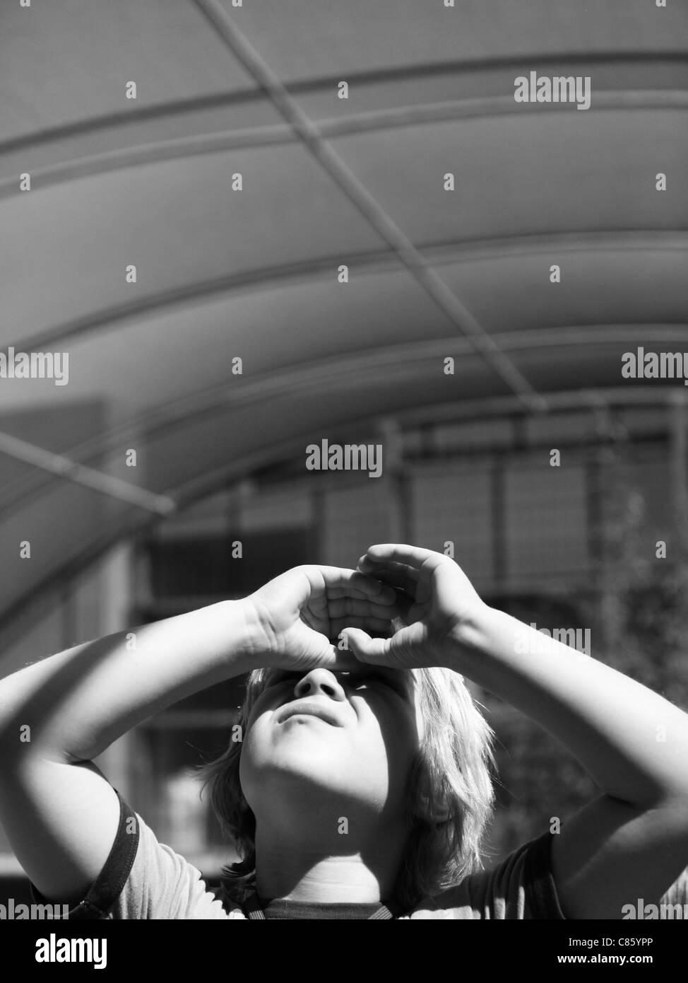 Little Boy ricerca di schermare il suo occhio dal sole Immagini Stock