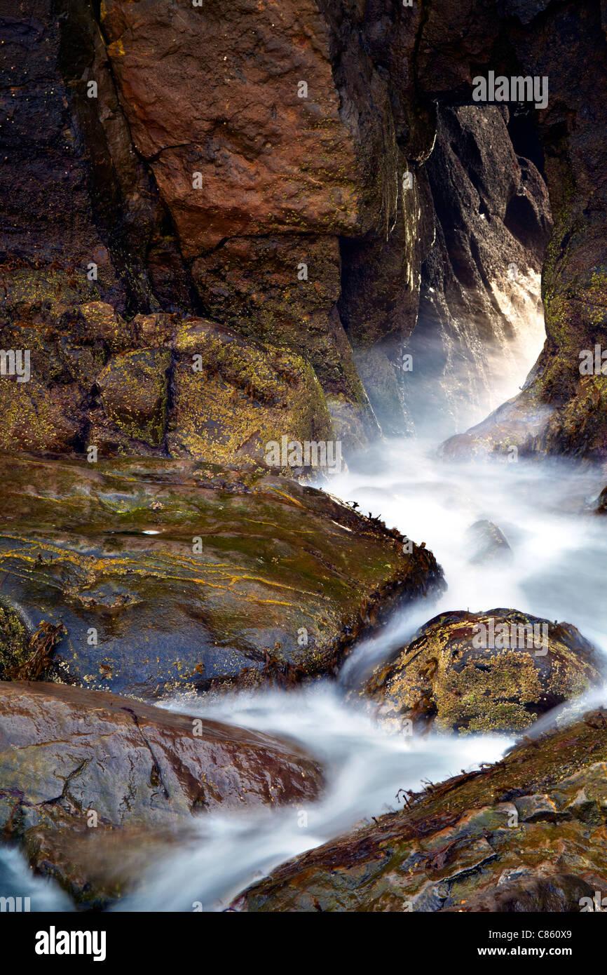 Acqua e rocce alle porte della Chiesa, Skrinkle Haven, vicino Tenby, Pembrokeshire. Immagini Stock