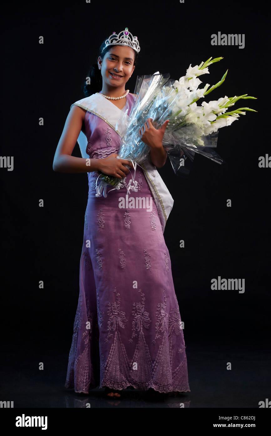Teenage regina di bellezza tenendo un mazzo di fiori Immagini Stock