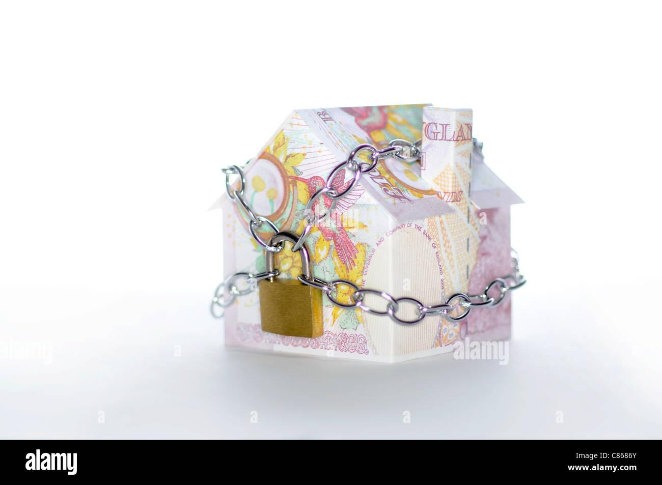 Modello di casa piegato con British pound banconote incatenati e bloccato Foto Stock