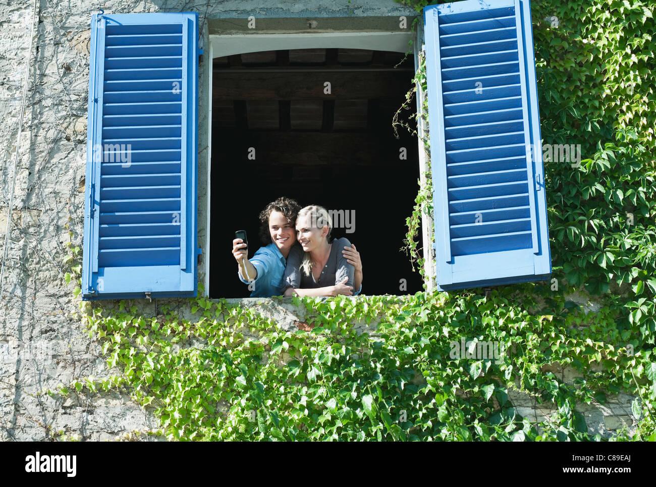 L'Italia, Toscana, coppia giovane fotografare in hotel windows con otturatore Immagini Stock