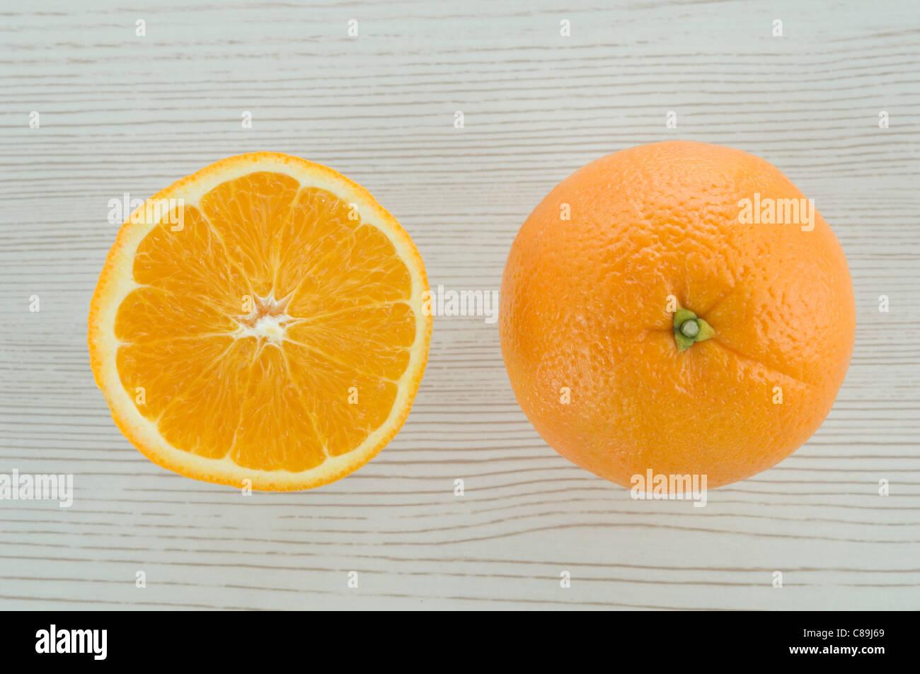 Tutta arancione e slice su sfondo di legno Immagini Stock