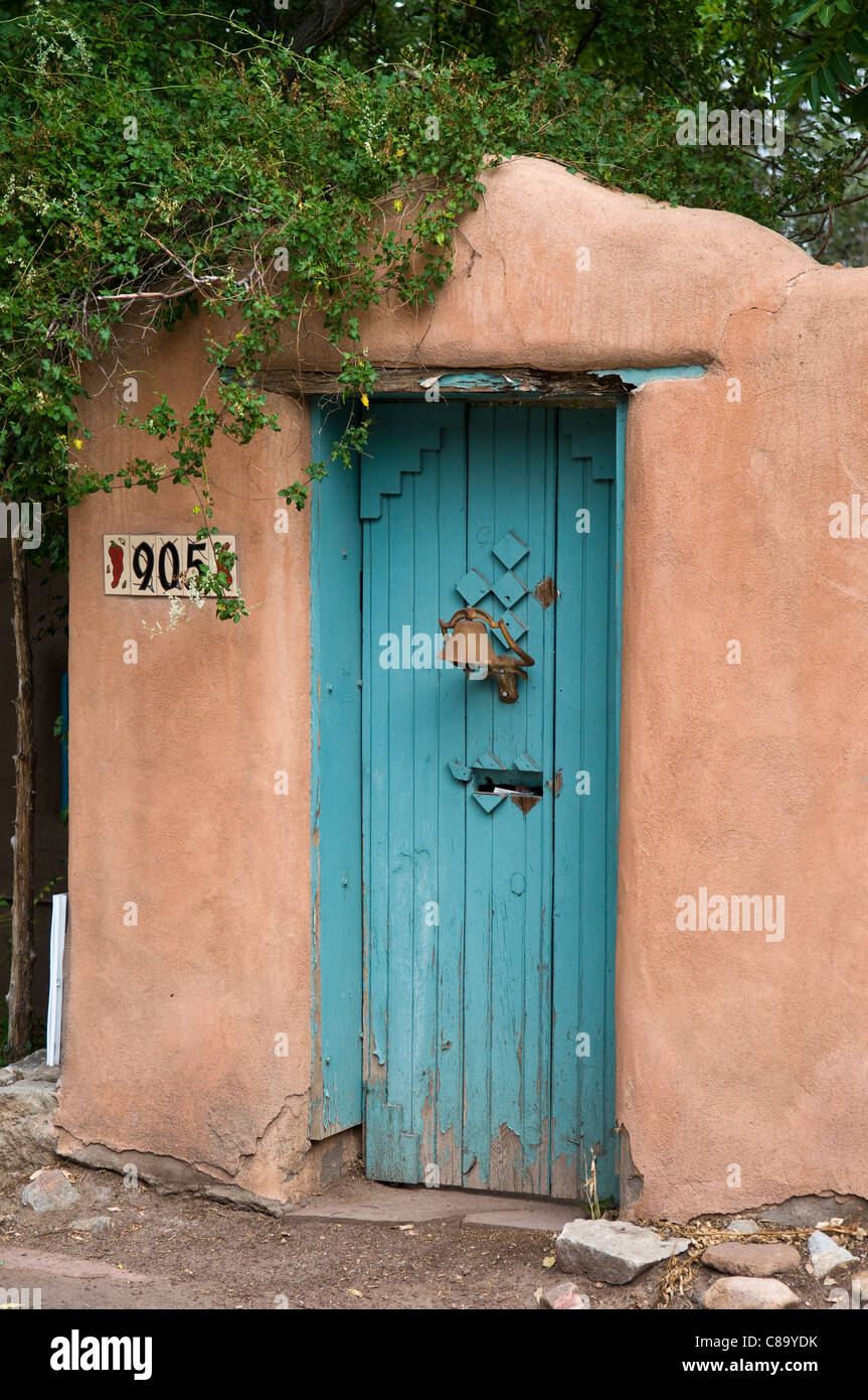Porta blu con campana in adobe muro in Santa Fe New Mexico USA America del Nord Immagini Stock