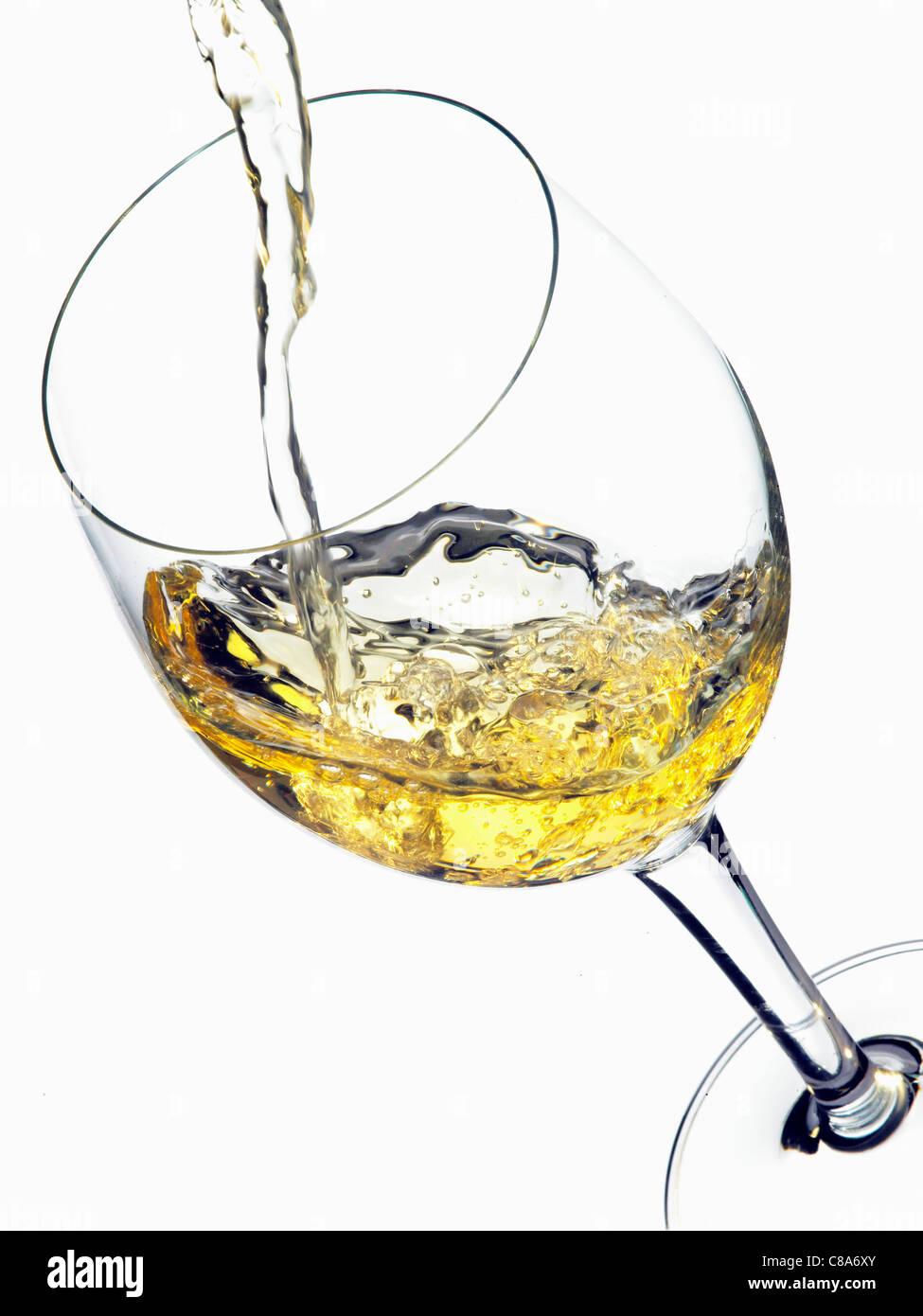 Versare il vino bianco in un bicchiere Foto Stock