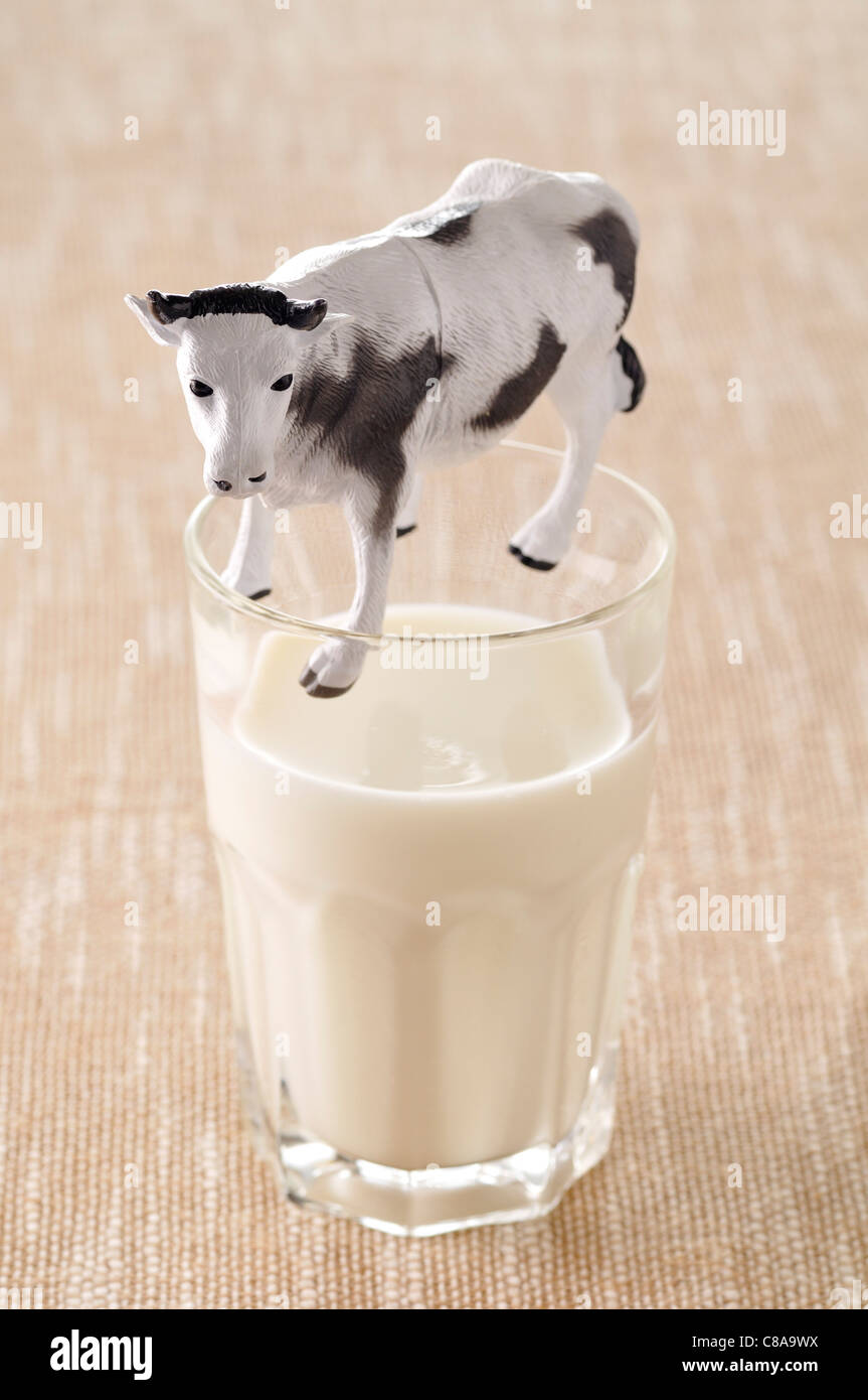 Bicchiere di latte e la mucca figurina Immagini Stock