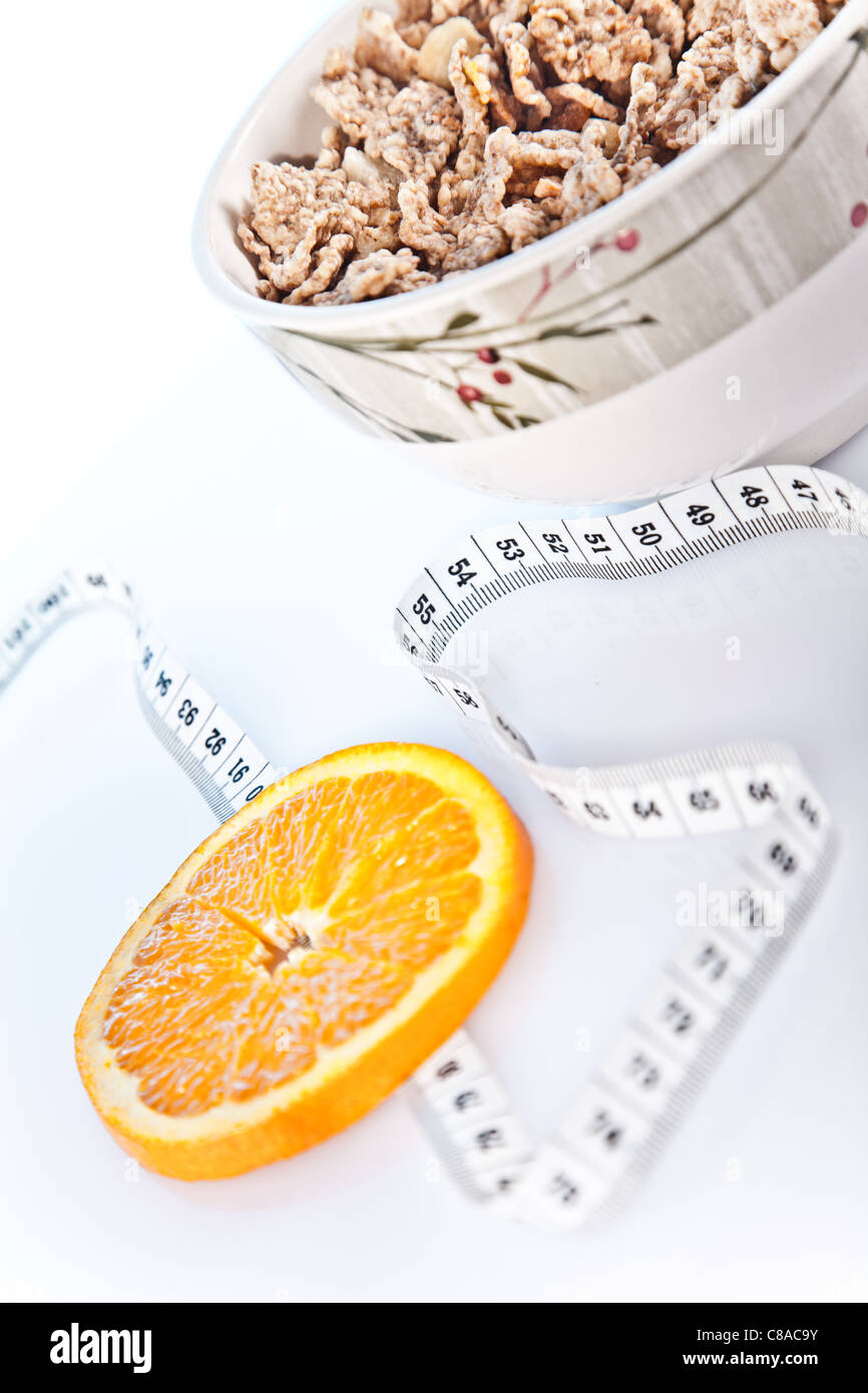 Fetta di orand , ciotola di cornflake e nastro di misurazione Immagini Stock