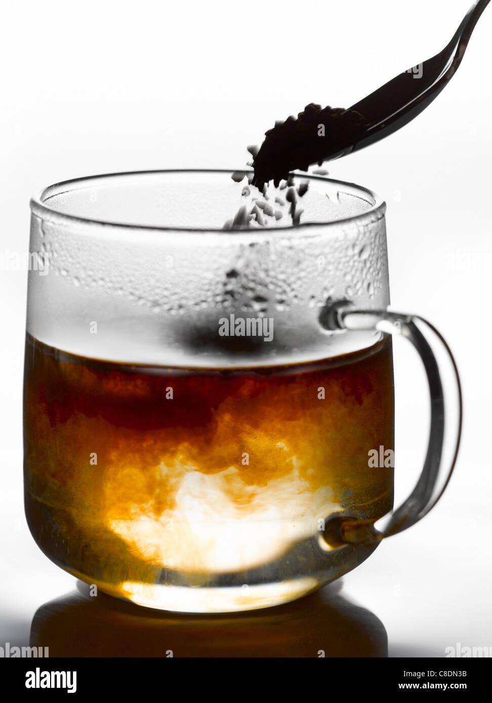 Aggiungere il caffè istantaneo per una tazza di acqua calda bollente Immagini Stock