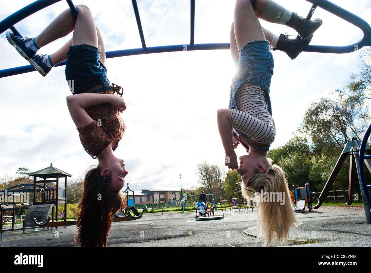 Due 16 17 anni, ragazze adolescenti, appeso a testa in giù in un parco giochi, REGNO UNITO Immagini Stock