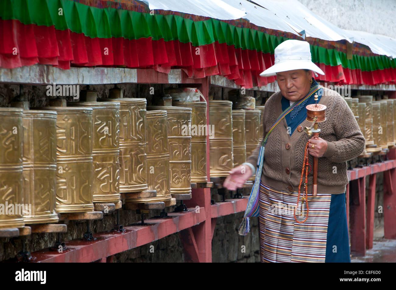 Vecchia donna camminando lungo il pregare ruote, Potala, Lhasa, in Tibet, in Cina Immagini Stock