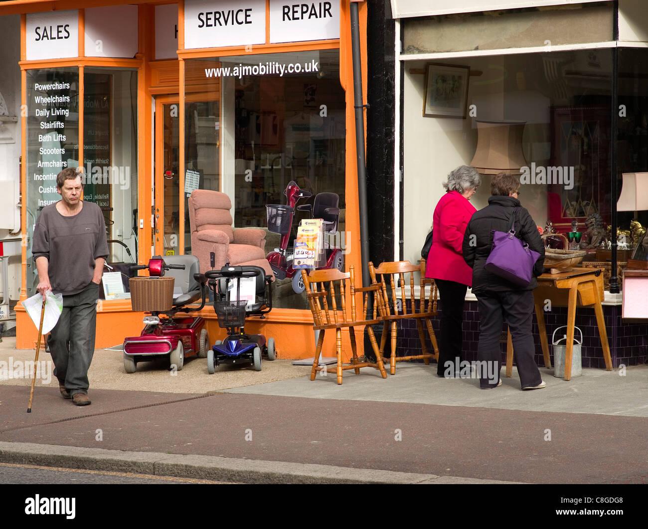 Anziani al di fuori di un piccolo negozio di vendita scooter di mobilità Immagini Stock