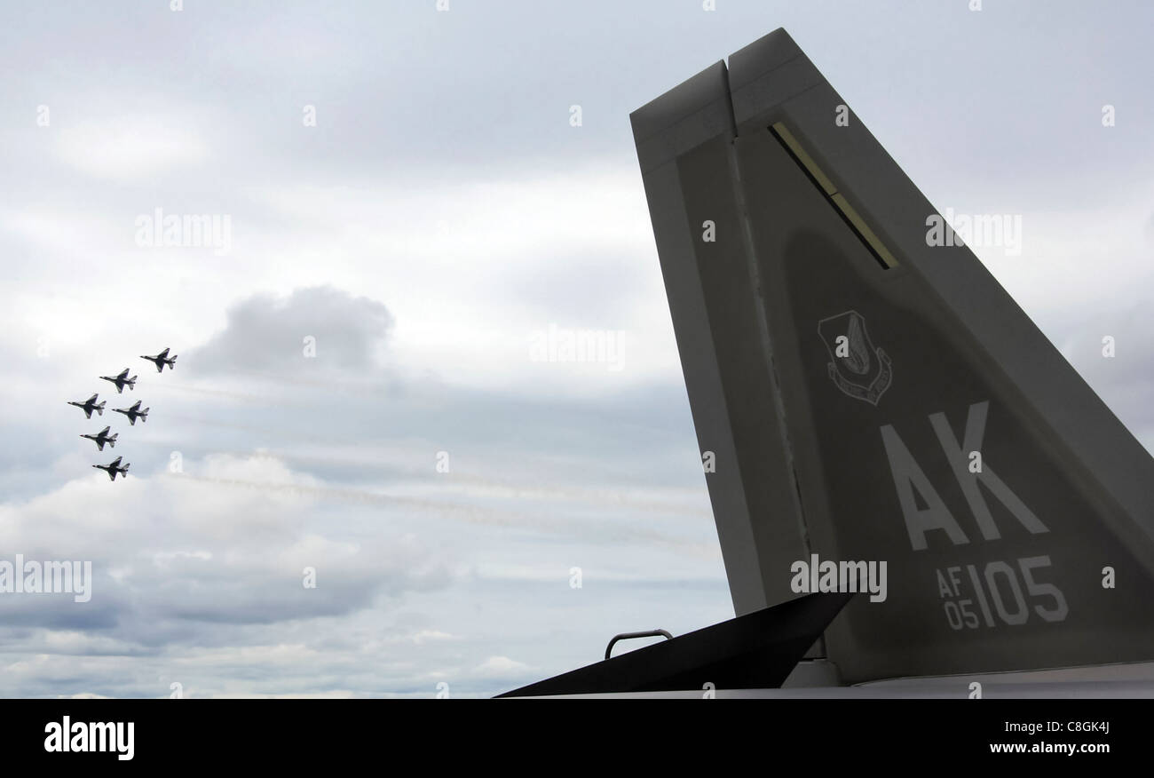"""Sei Air Force Thunderbird F-16 Fighting Falcons volano insieme in formazione dietro il F-22 Raptor per più di 6,000 spettatori durante l'airshow del giugno 24 alla base dell'aeronautica Eielson Alaska. Lo spettacolo aereo """"Saaring into Soltice"""" ha offerto alla comunità locale l'opportunità di visitare e ammirare da vicino le capacità dell'aereo dell'Aeronautica militare. Foto Stock"""
