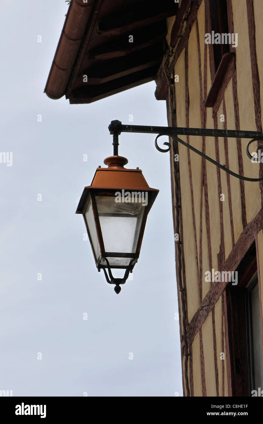 Vecchio stile lanterna metallica su un crogiolarsi muro di casa con un cielo nuvoloso Immagini Stock