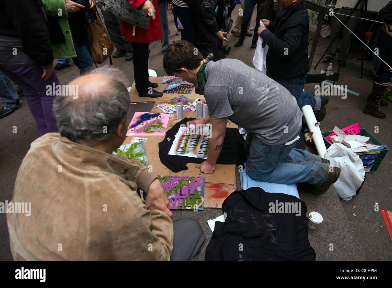 """Occupare Wall Street protester verniciatura a spruzzo """"occupare WALL STREET"""" su una T-shirt nera all'interno Immagini Stock"""