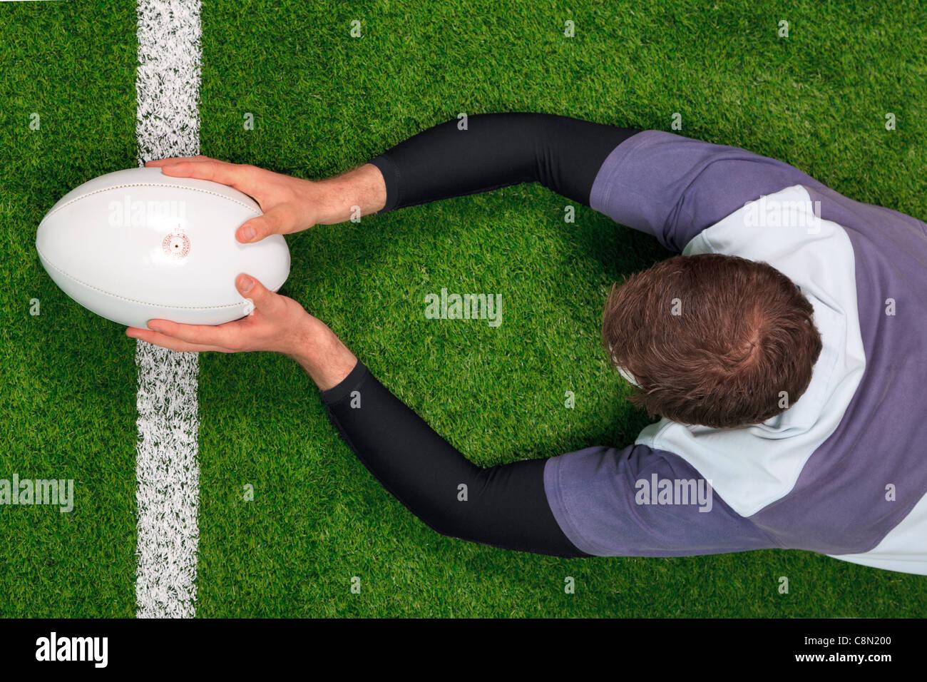 Foto aerea di un giocatore di rugby immersioni subacquee al di sopra della linea di cliente a provare con entrambe Immagini Stock