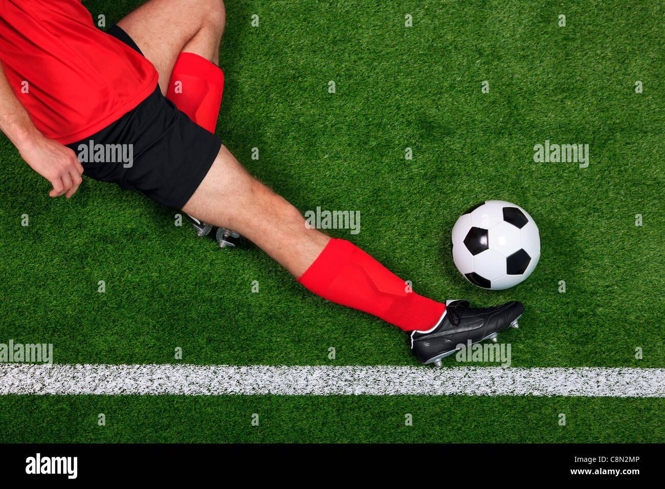 Foto aerea di una partita di calcio o giocatore di calcio in scorrimento per salvare la palla andando oltre il diversivo Immagini Stock