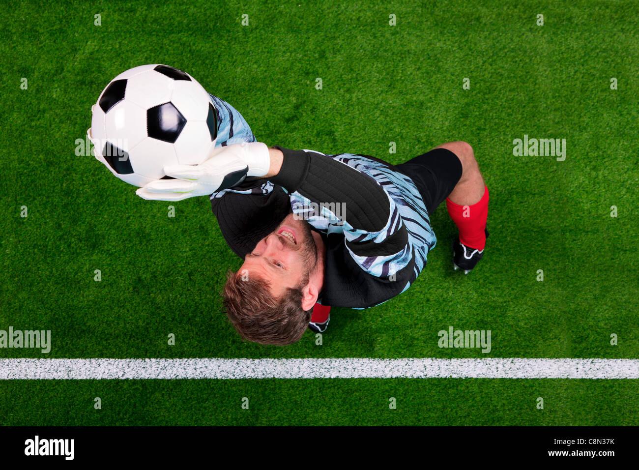 Foto aerea di un portiere di calcio di saltare in aria il salvataggio la sfera sulla linea. Punto di messa a fuoco Immagini Stock