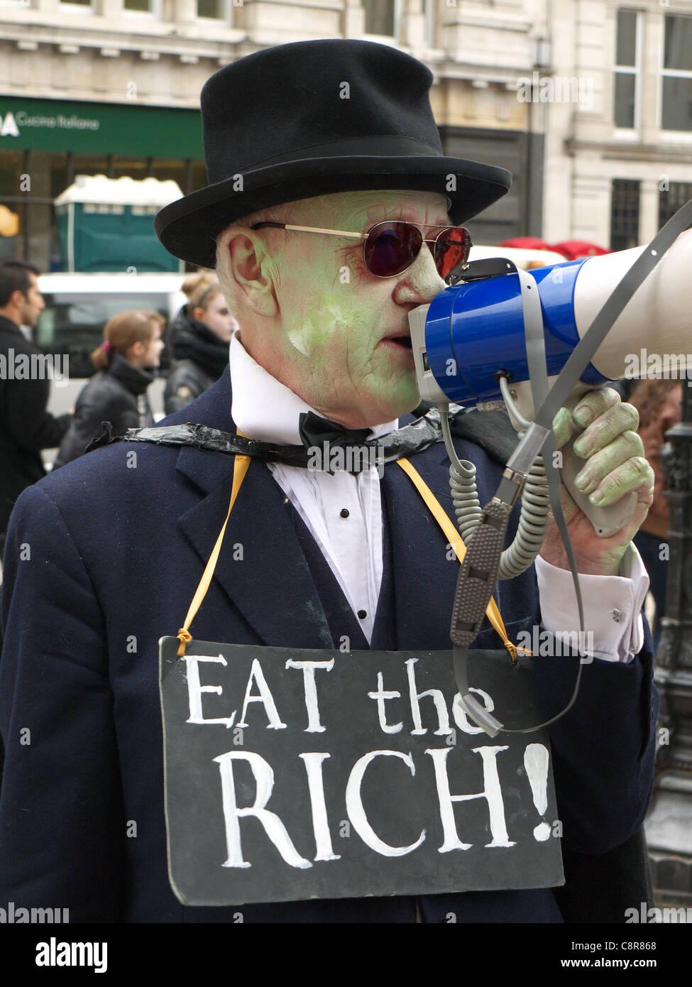 """Un manifestante con un """"mangiare il ricco!"""" segno ad un anti-capitalista protestare Immagini Stock"""