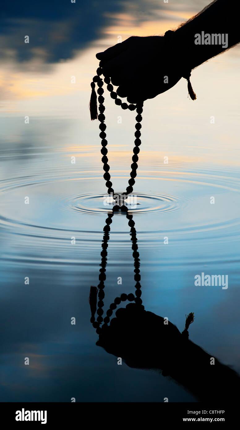 Mano azienda Rudraksha indiano / Japa Mala i grani di preghiera su acqua increspata . Silhouette Immagini Stock