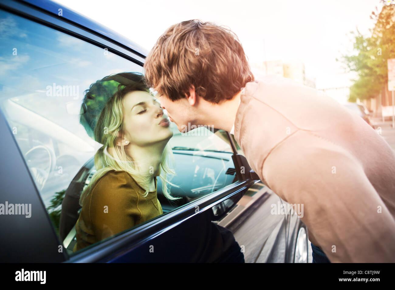 Stati Uniti d'America, Washington, Seattle, coppia giovane kissing attraverso la finestra della macchina Foto Stock