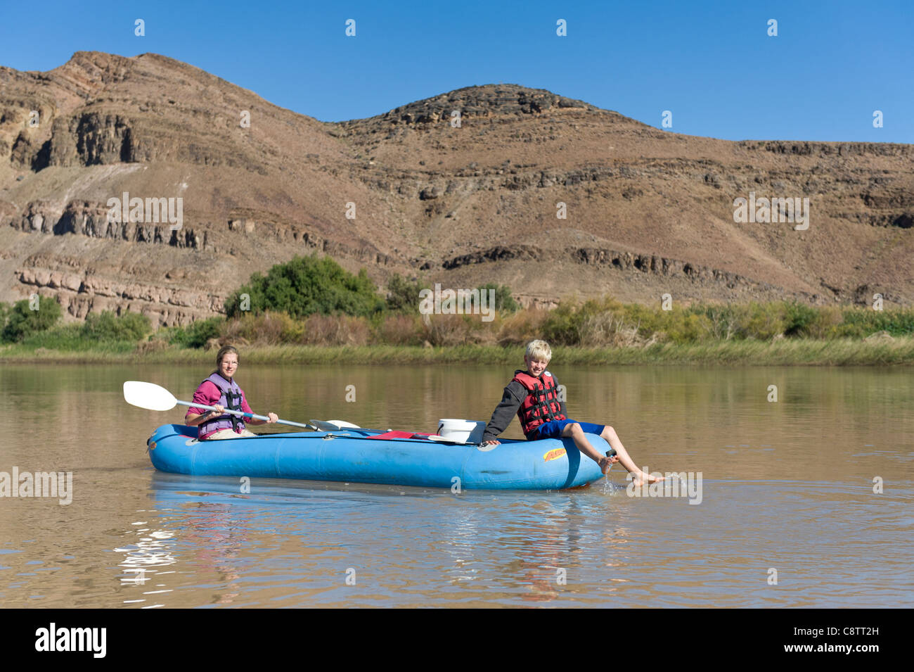 La madre e il bambino godere giù il fiume Oranje a Noordoewer Namibia Immagini Stock