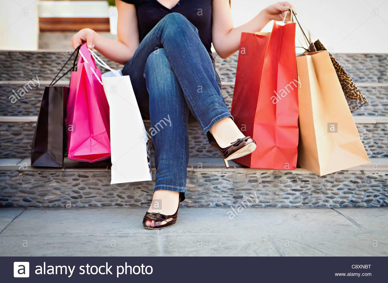 Stati Uniti, California, Lawndale, Donna seduta sui gradini con borse per lo shopping Immagini Stock