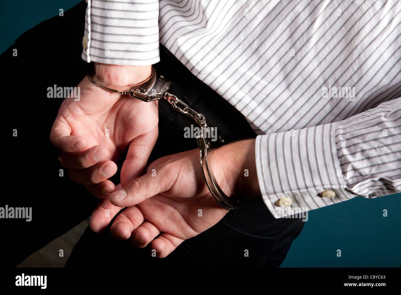 Un collare bianco penale in manette su sfondo blu. Immagini Stock
