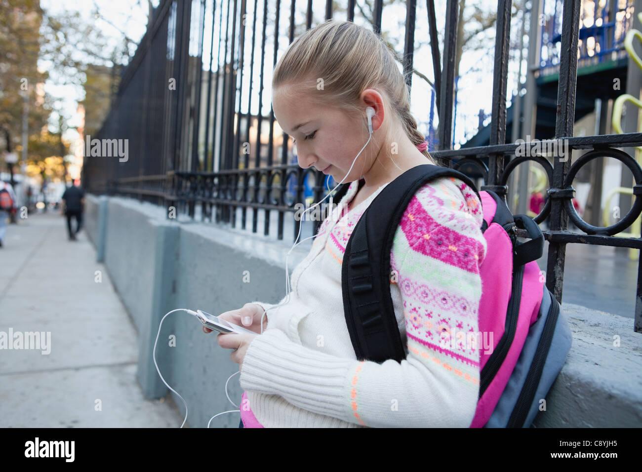 Stati Uniti d'America, nello Stato di New York, New York City, ragazza (10-11) con gli auricolari e ascolto Immagini Stock