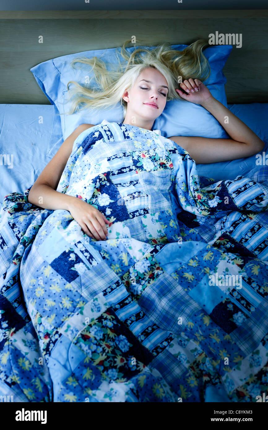 Giovane donna che dorme tranquillamente di notte a letto Immagini Stock