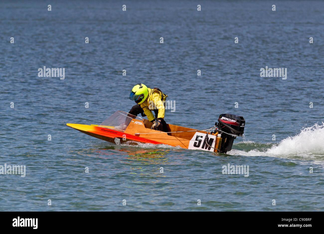 Uomo accelerando lentamente powerboat e il bilanciamento del peso con la potenza del motore. Immagini Stock