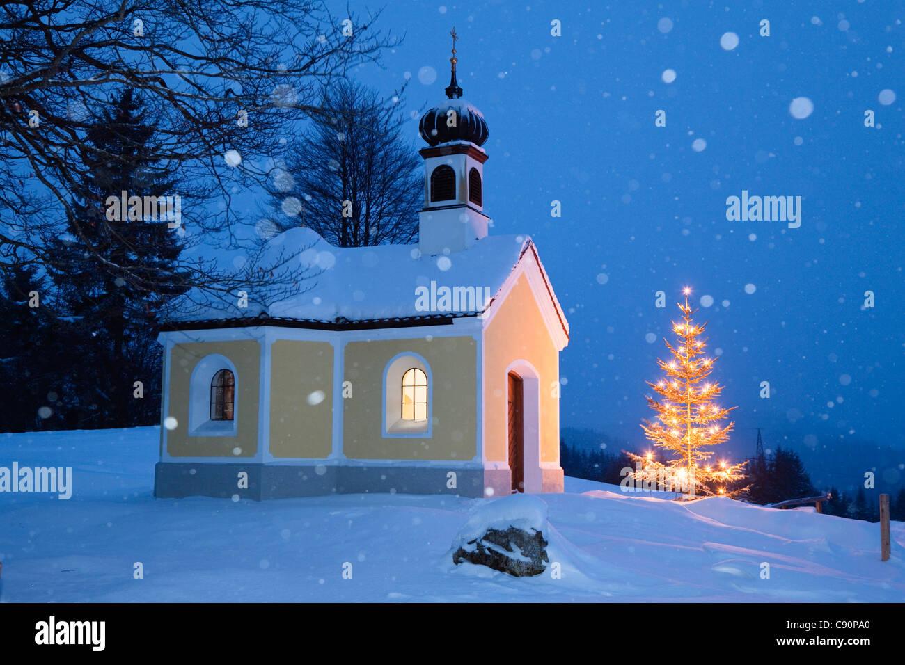 Cappella con albero di natale a nevicata, Alta Baviera, Germania, Europa Immagini Stock