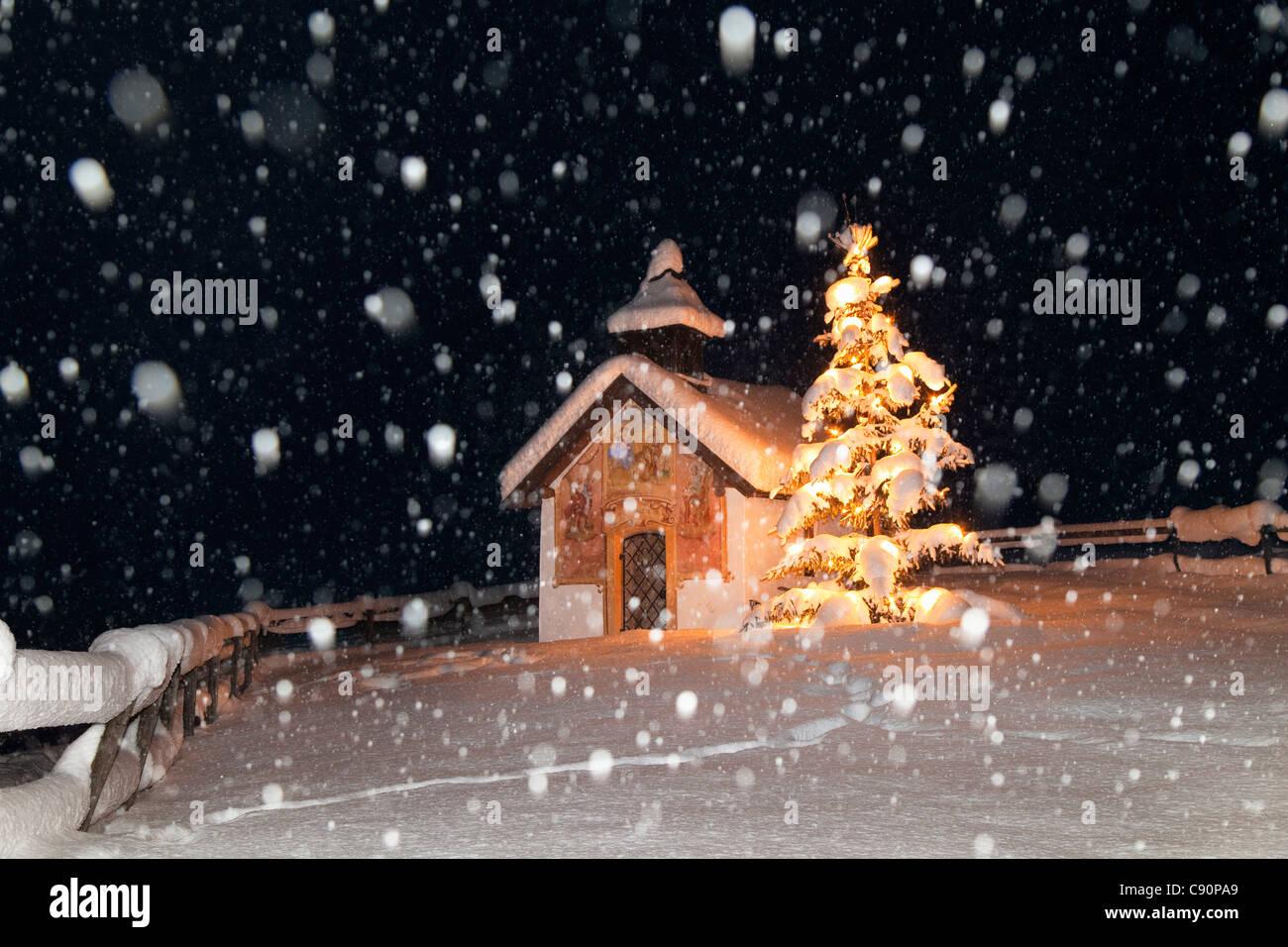 Cappella con albero di natale a nevicata, Elmau, Alta Baviera, Germania, Europa Immagini Stock