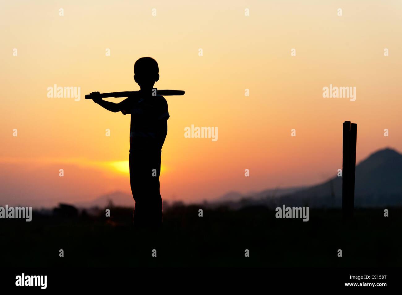 Silhouette di un giovane ragazzo indiano a giocare a cricket contro un sfondo al tramonto Foto Stock