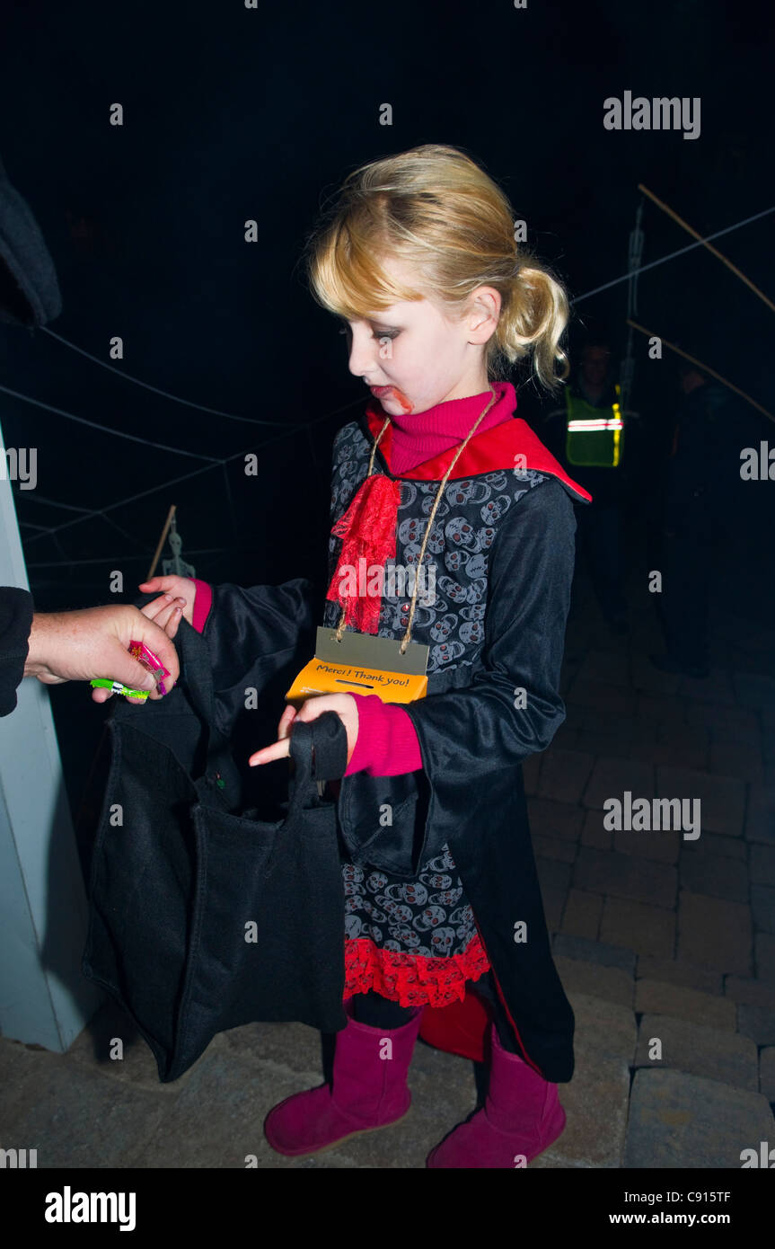 Bambino raccogliere caramelle durante il trucco e trattare alla notte di Halloween in Canada Immagini Stock