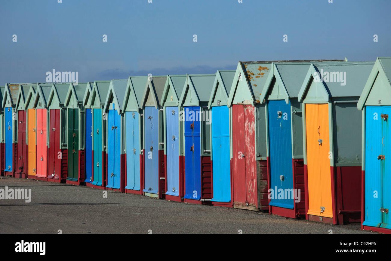 Brighton ha righe di coloratissimi beachhuts sul lungomare. Le porte sono dipinte in colori luminosi. Foto Stock