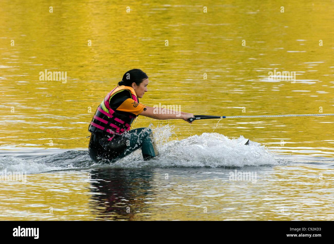 Una femmina di acqua sciatore trainato da una barca accelerando sul lago Batchworth Rickmansworth Aquadrome Herts Immagini Stock