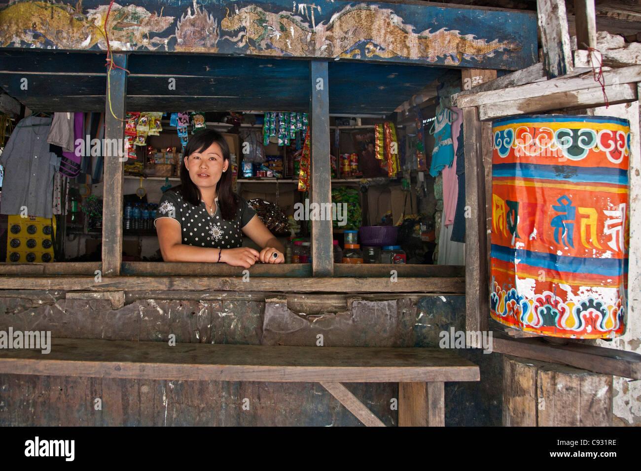 Una donna al negoziante nel suo piccolo negozio rurale sulle rive del fiume Kolounchu appena fuori Trashigang. Immagini Stock