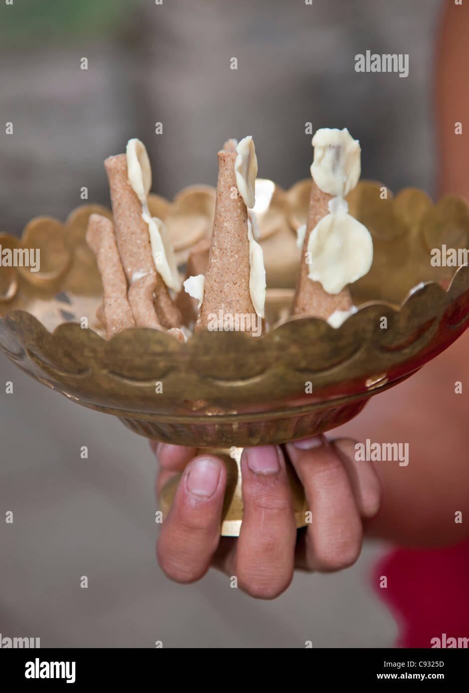 Un monaco trattiene un piatto di ottone contenente torte rituale (torma) e burro come una simbolica offerta a divinità Immagini Stock