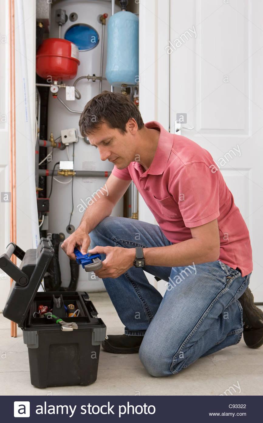 Tuttofare con una chiave inginocchiata davanti toolbox nella parte anteriore della caldaia in armadio Immagini Stock