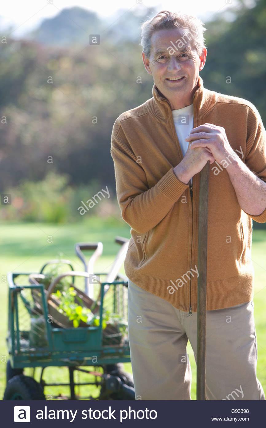 Ritratto di sorridente uomo senior con utensili da giardinaggio Immagini Stock