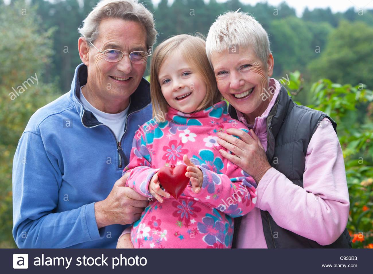 Ritratto di sorridere i nonni e nipote con cuore di ornamento di forma in giardino Immagini Stock