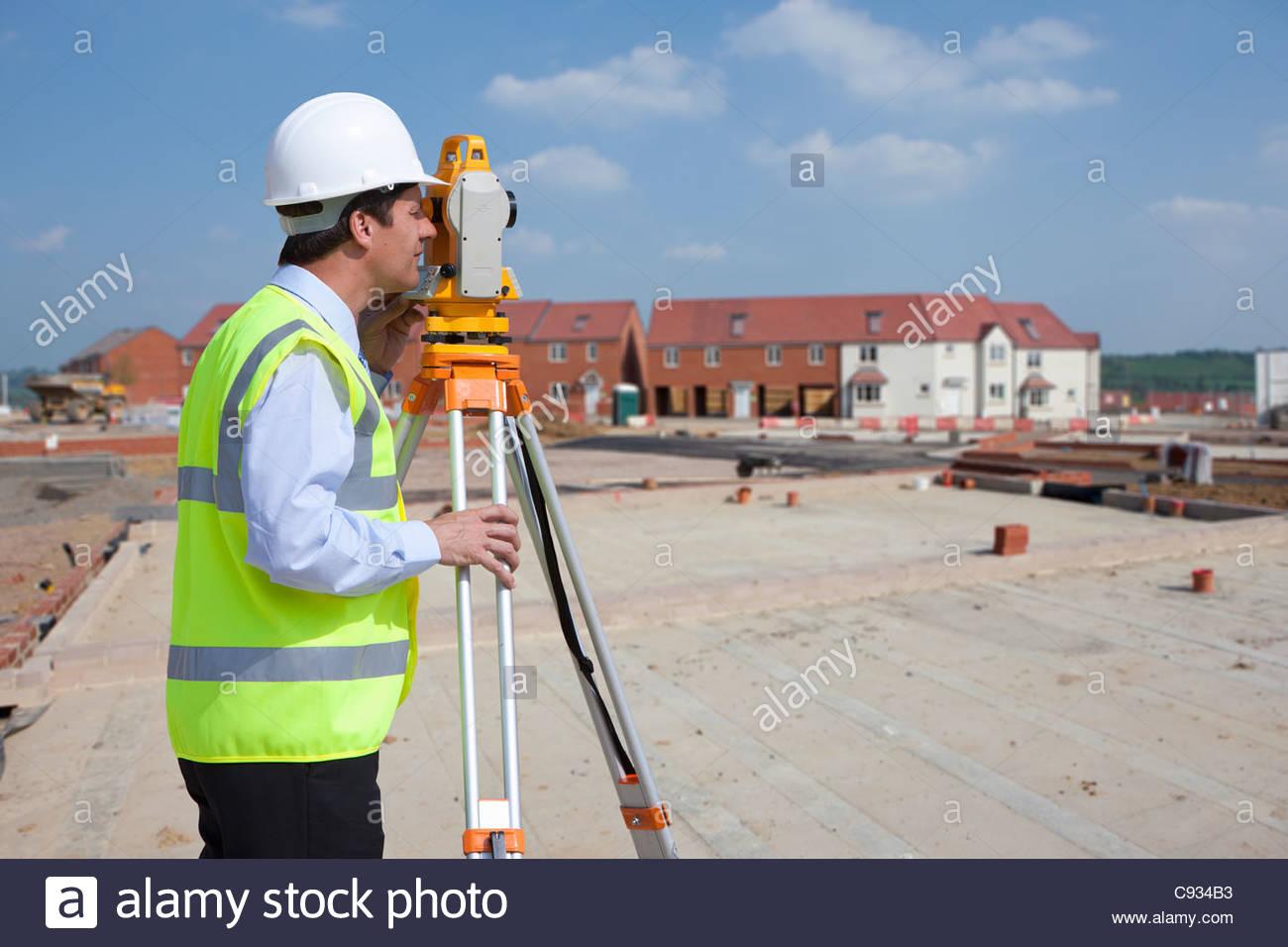 Geometra utilizzando teodolite al sito in costruzione Immagini Stock