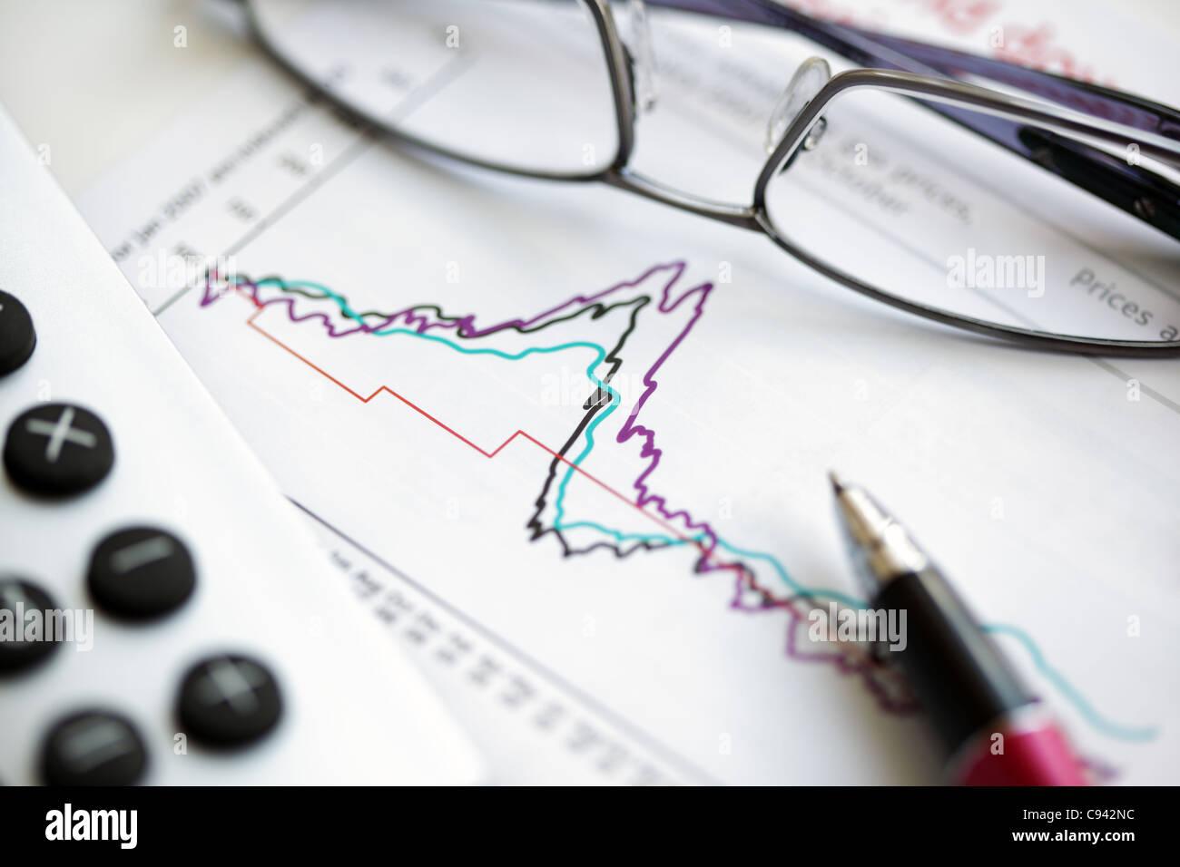 Occhiali di penna e calcolatrice sul grafico azionario Immagini Stock