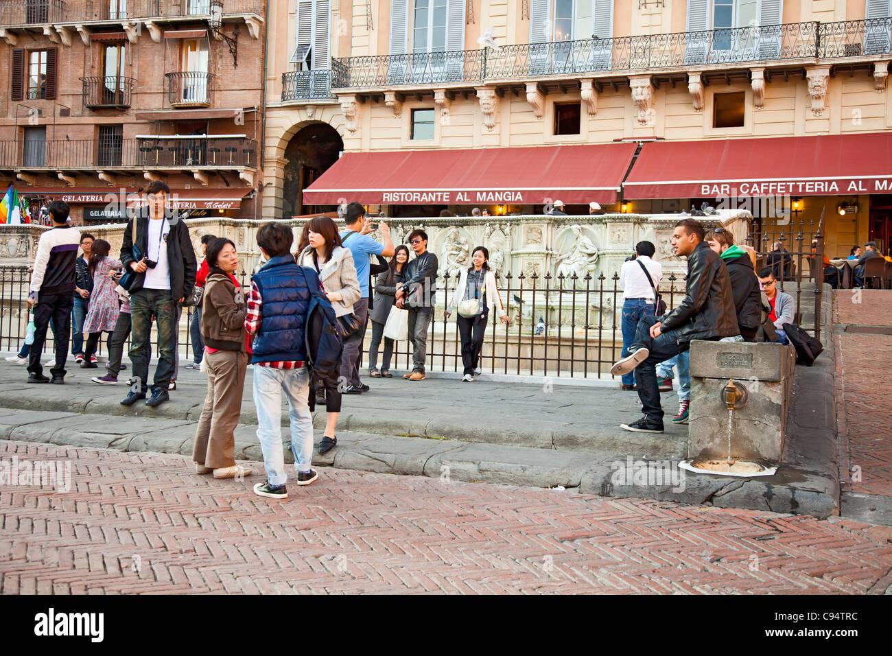 Turisti alla Fonte Gaia, Piazza de Campo nel centro di Siena, Toscana, Italia. Si tratta di un ben noto luogo di Immagini Stock