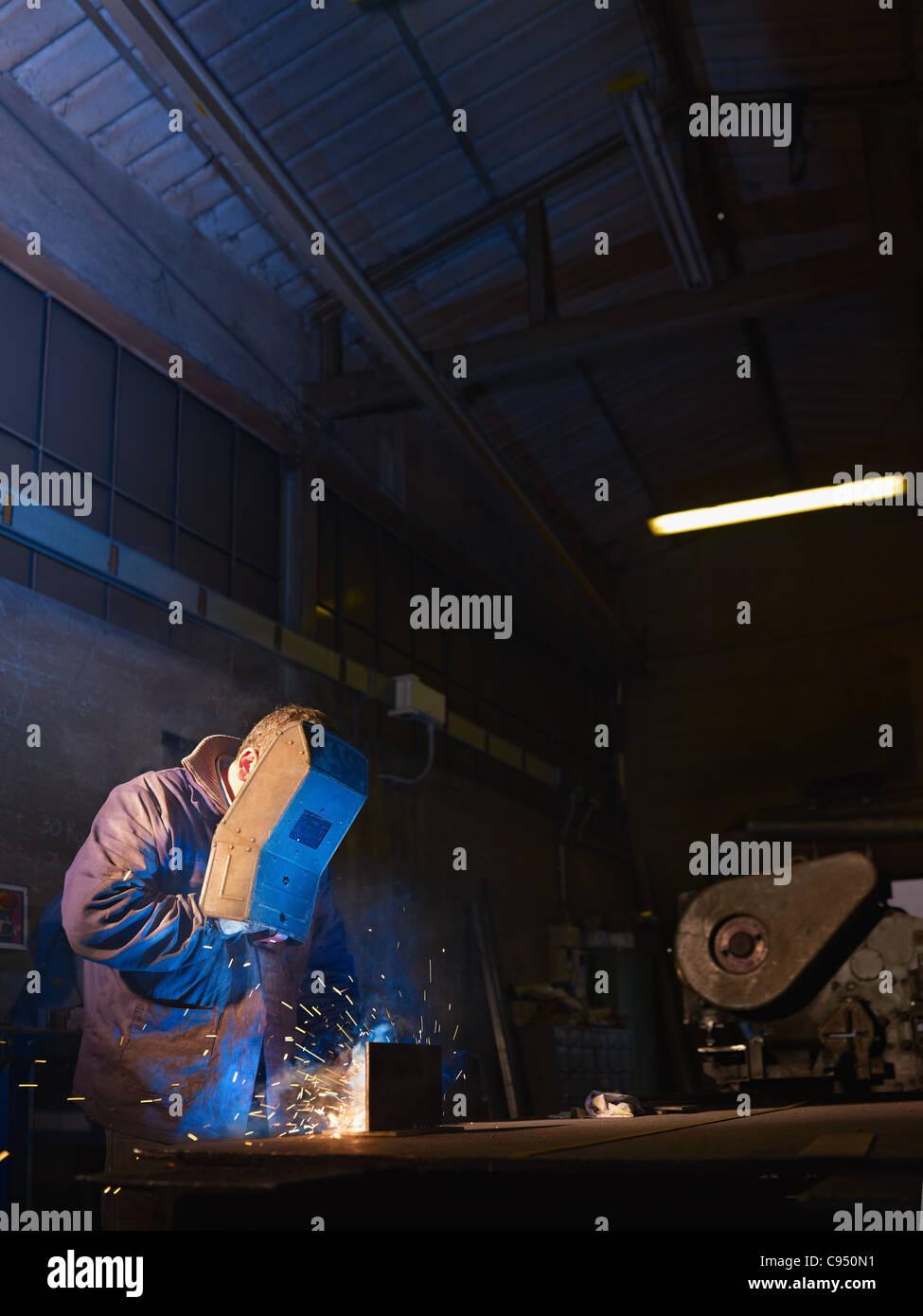 Lavoratore manuale nella fabbrica di acciaio utilizzando la maschera di saldatura, strumenti e macchinari in metallo. Immagini Stock