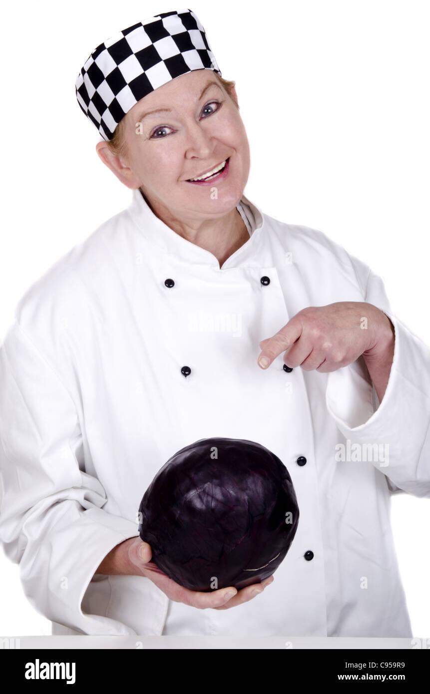 Lo chef femmina mostra con il suo dito indice su un cavolo rosso Immagini Stock