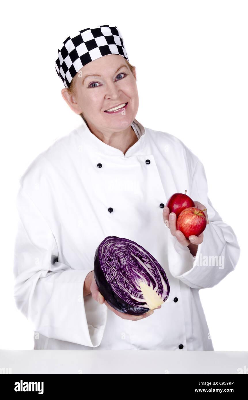 Lo chef femmina tenendo un cavolo rosso e due mele nelle sue mani prima della cottura Immagini Stock