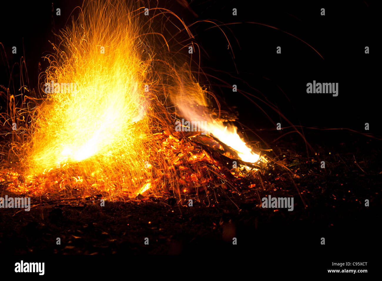 Il fuoco con le fiamme e scintille. Colore arancione intenso, giallo bagliore del falò contro una notte nera Immagini Stock