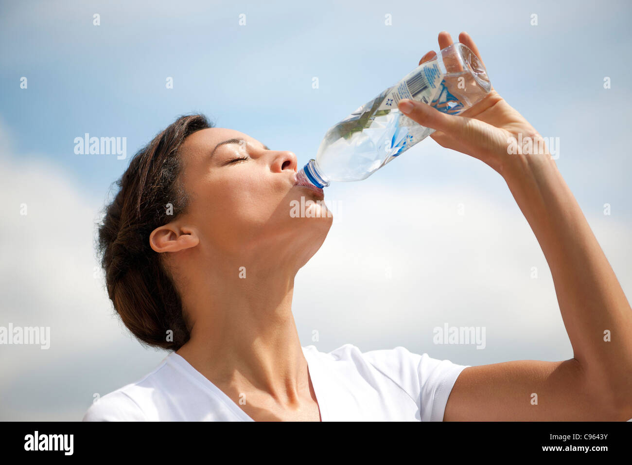 Donna di bere acqua in bottiglia. Immagini Stock